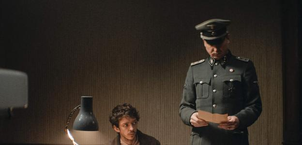 Still from the film Persian Lessons, with a concentration camp prisoner seated at a desk and a Nazi officer standing over him.